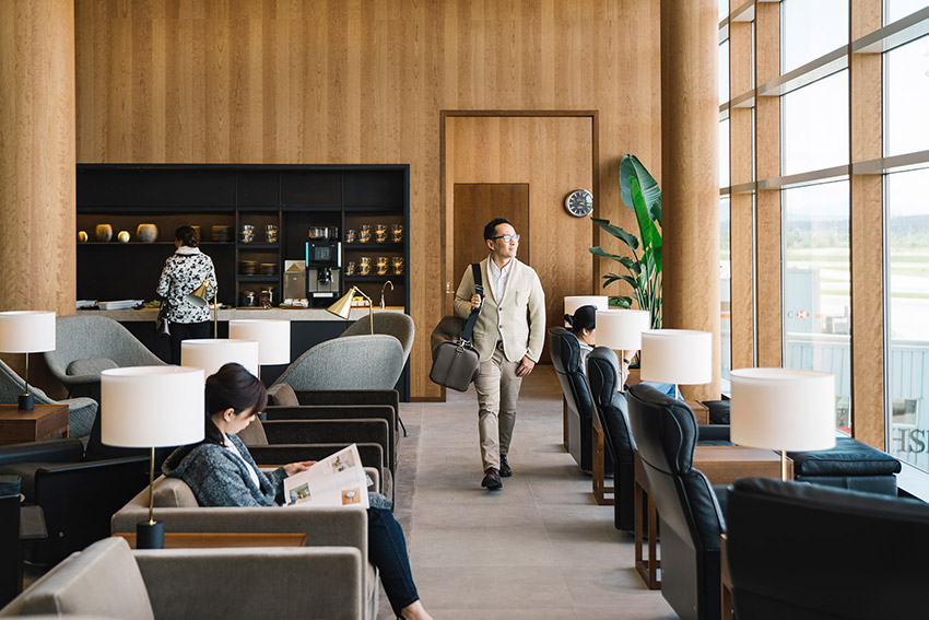 asian man enjoying the outside view from within the contemporary interior design of the cathay pacific lounge