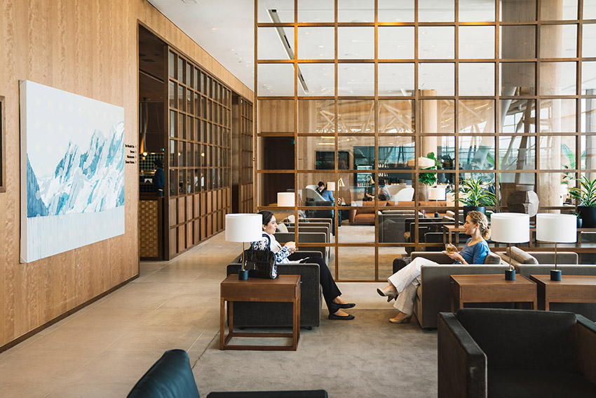 2 ladies relaxing and talking in beautiful interior designed cathay pacific lounge in vancouver international airport