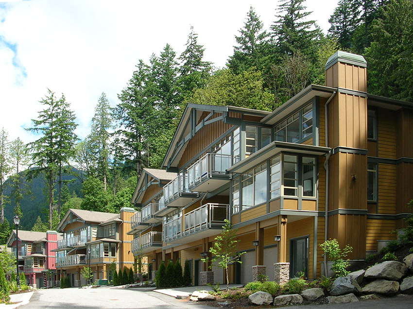 front view of luxury townhome complex with large trees in the background