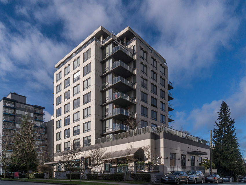 full view from across the street of midrise condominium in west end vancouver