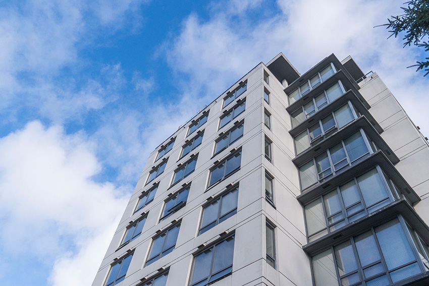 view looking up at side and corner of midrise condominium complex